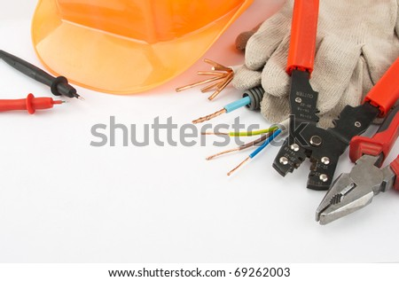 Electrician's tools. Hardhat, pliers, cables, cutter, etc. - stock photo