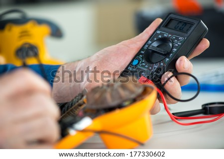 Electrician using Digital Voltmeter for Testing Voltage on old hair dryer. Close Up. Selective focus. - stock photo