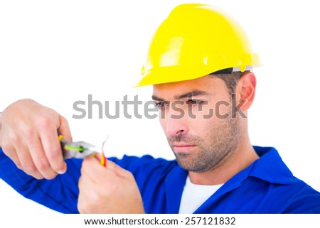 Electrician wearing hard hat while cutting wire with pliers over white background - stock photo