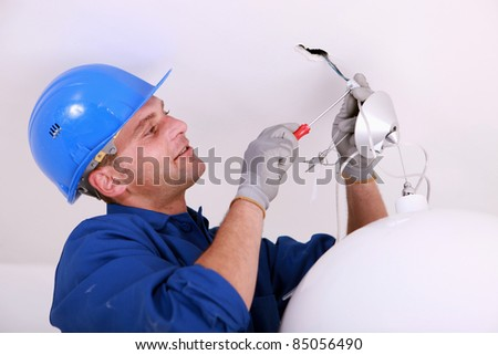 Electrician wiring a ceiling light - stock photo