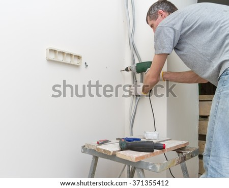 Electrician with a drill in the process of laying cables. - stock photo