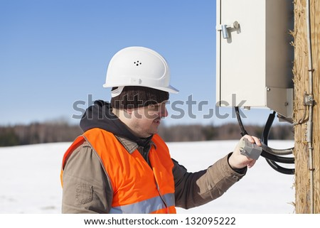 Electrician with electrical cable in the hands near switchboard - stock photo