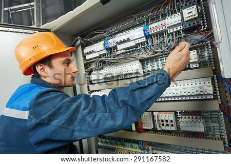 electrician with screwdriver tighten up switching electric actuator equipment in fuse box - stock photo