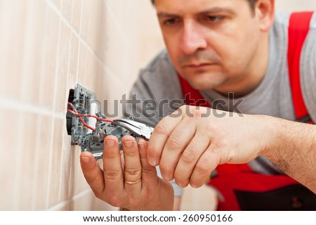 Electrician working on electrical wall fixture - inserting the wires, closeup - stock photo