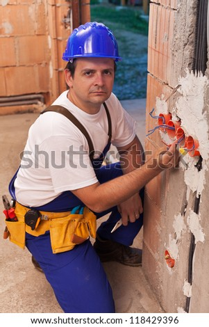 Electrician working with wires in a new building - stock photo