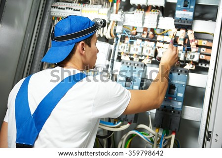 electrician works with electric meter tester in fuse box - stock photo