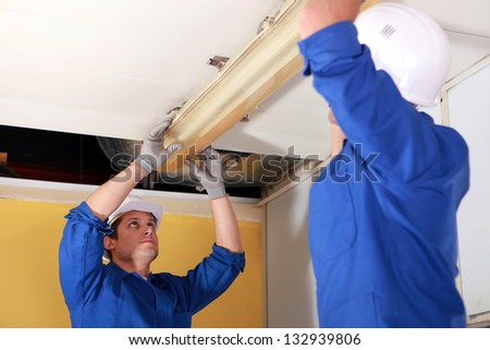 electricians fixing neon on the ceiling - stock photo