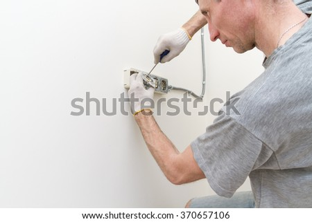 Electricians in the process of mounting electrical outlets. - stock photo