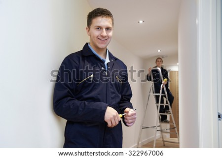 Electricians Installing Ceiling Lights In Domestic Home - stock photo