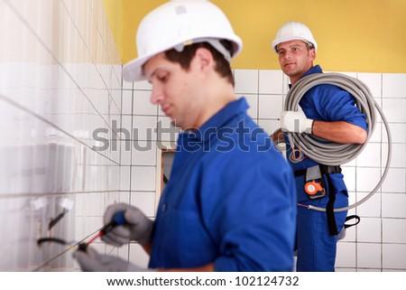 Electricians plumbing a bathroom - stock photo