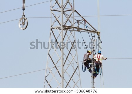 Electricians repairing high tension tower cable