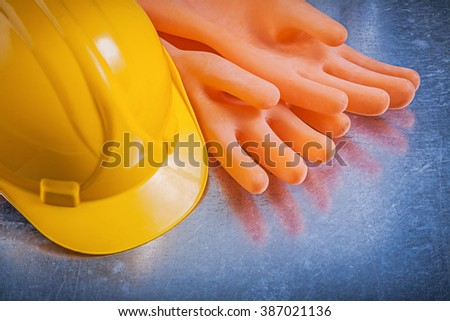 Electricians rubber gloves hard hat on metallic background electricity concept.