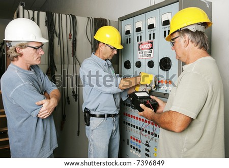 Electricians working on an industrial power distribution center while supervisor watches.  All work being performed according with industry code and safety standards. - stock photo