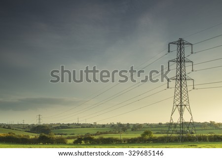 Electricity lines carrying power across the countryside of England as the evening sun begins to set. - stock photo