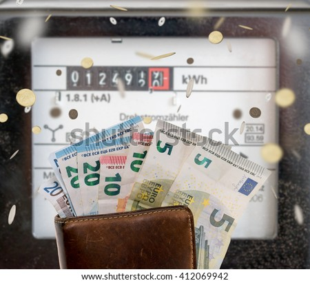 electricity meters and a wallet with euro banknotes and coins / electricity meters - stock photo