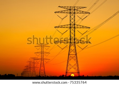 Electricity Pillars against a colorful yellow sunset - stock photo