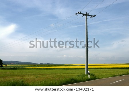 electricity pole in rural field - stock photo