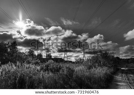 Electricity poles in meadow. Power of electricity. Industry and nature. Cloudy sky and sun.