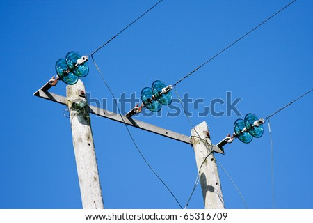 Electricity Poles with Wires and Green Glass Insulators against Deep Blue Sky