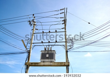 Electricity post and distribution transformer box on the blue sky. - stock photo