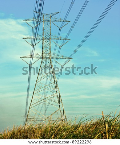 electricity pylon in field - stock photo