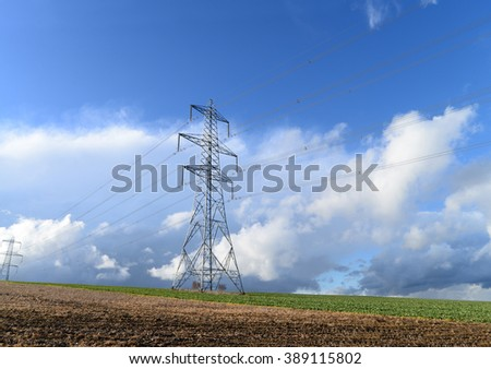 Electricity pylon in field against dramatic blue sky