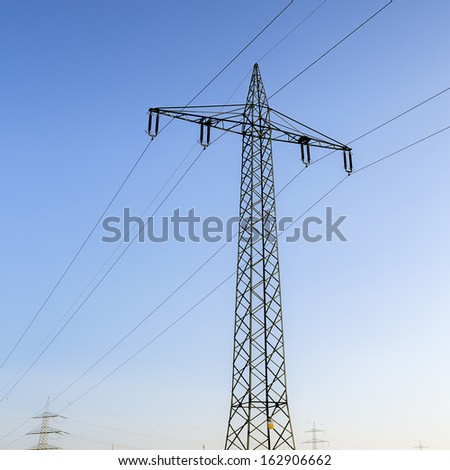 Electricity pylon power pole high voltage against blue sky and sunset