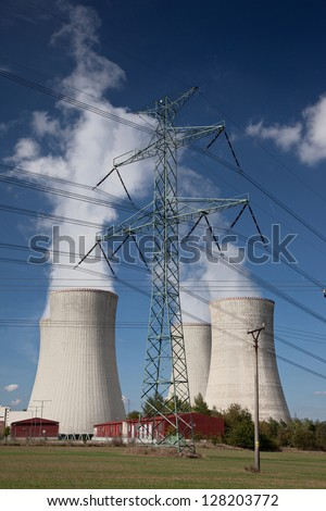 Electricity pylon with power plant cooling tower background - stock photo