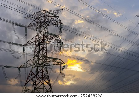 Electricity pylons and cable lines during sunset  - stock photo