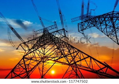 electricity pylons and lines at dusk - stock photo