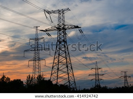 Electricity pylons and lines at dusk at sunset - stock photo