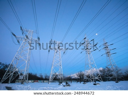 Electricity pylons and power high voltage power tower in winter evening - stock photo
