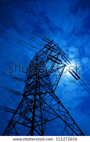 Electricity pylons on blue sky and sun rays - stock photo