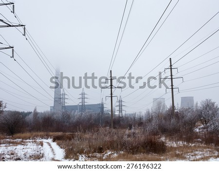 Electricity pylons, power lines, smoke stack and cooling tower of the cogeneration plant near Kyiv (Ukraine). - stock photo