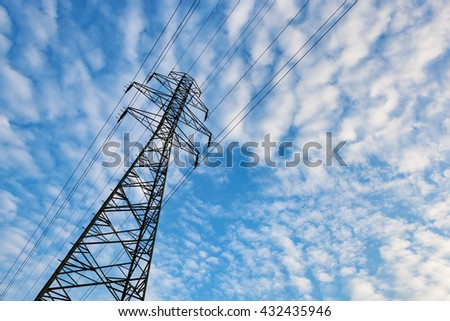 Electricity transmission pylon against blue sky with fluffy clouds. Copyspace - stock photo
