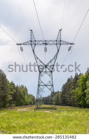 Electricity transmission pylon and power lines in a forest - stock photo