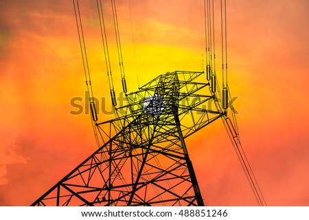 Electricity transmission pylon silhouetted against sunset sky.