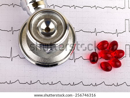 Electrocardiogram graph report with stethoscope and pills on it - stock photo