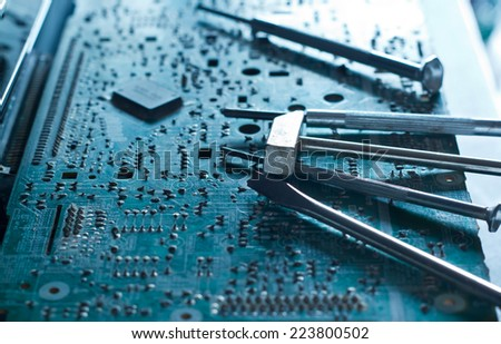 Electronic board and tools repairs, toned blue concept - stock photo