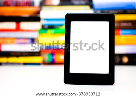 Electronic book reader on background of books - stock photo