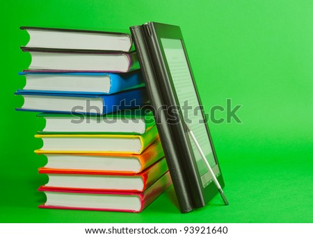 Electronic book reader with stack of printed books over green background - stock photo