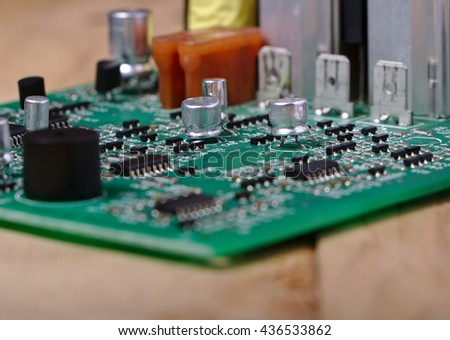 Electronic circuit board with microprocessor , semiconductor and components on wooden desk background. - stock photo