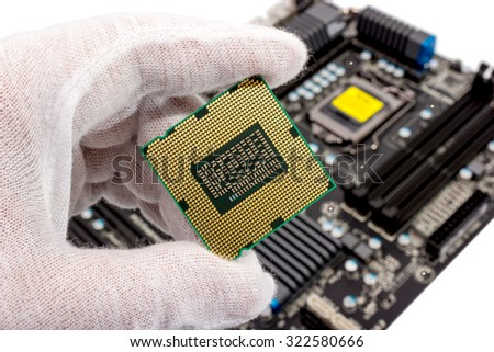 Electronic collection - The repairman holding CPU in hand before installation into the motherboard - stock photo
