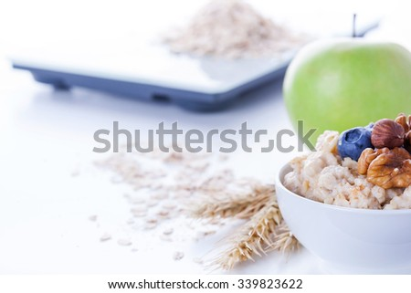 Electronic digital kitchen scale with oatmeal, apple and measuring tape. Healthy nutrition concept