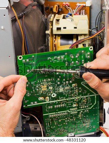electronic laboratory, technician repairs circuit board of tube television with iron soldering and tin wire - stock photo