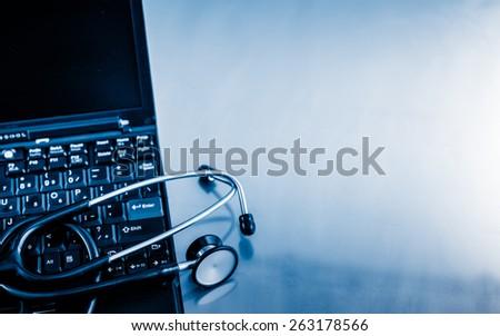 Electronic medical, stethoscope on PC/Laptop/Keyboard blue toned images. - stock photo