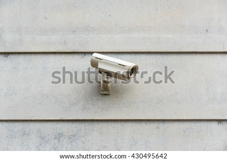 Electronic safe camera on white wall. Security equipment and technology