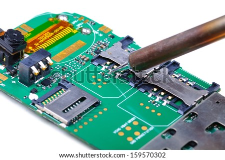 Electronic technician repairs SIM slot on mobile phone circuit board. Close-up with selective focus and Shallow Depth of Field. Isolated on white background.