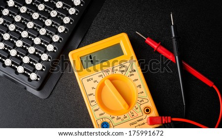 electronic tester and LEDs on a dark background - stock photo