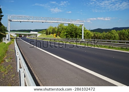 Electronic toll gate over a highway in a wooded landscape. White trucks, bridge and forested mountains in the background. White clouds in the blue sky. - stock photo